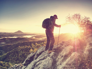 Climbing hiker with backpack in mountains. Rock climber