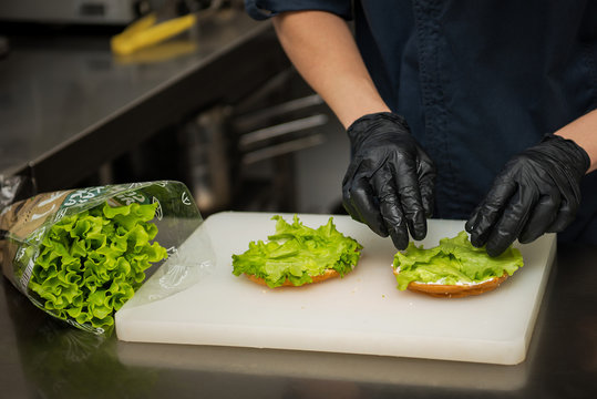chef making vegetarian sandwich with fresh lettuce, on a white bagel wearing black gloves