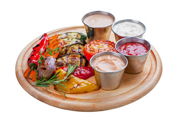 A set of grilled vegetables with different sauces. On a wooden Board and white background