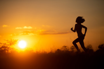 woman runner running with sunset background