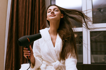 happy young girl dries her long thick hair with a black hairdryer