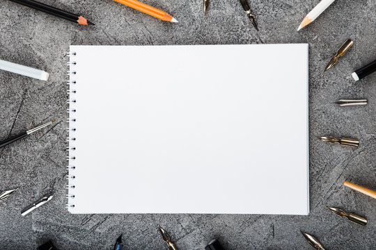 Artist home office desk workspace frame paint brushes and tools on gray background. Flat lay, top view creative minimal mock up template. Mockup Download.