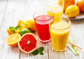 Glasses of juice and citrus fruits