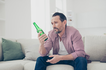 Man with sad face looking at the bottle sit on cosy couch in den