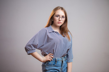 Confident young student girl wearing glasses and looking at the camera. Successful Redhead woman in a striped blouse and blue jeans. Youth, College, business