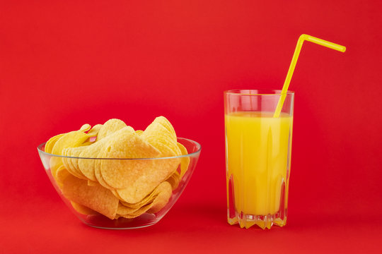 Bowl of potato chips and glass of orange drink in bright red background. Minimalistic image of attention grabbing snacks and beverage in vivid colors