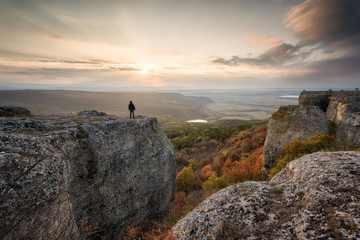 Sunset from the top / Silhouette of a woman on the top of a rock enjoys the view of sunset over an autumn forest