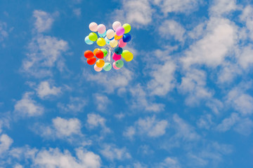 flying colorful toy balloon on a blue sky