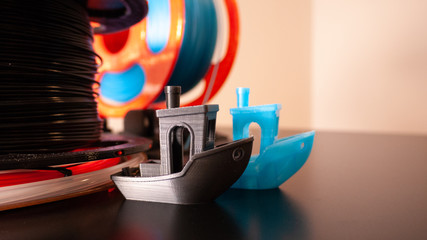 Fototapeta Two 3D printed boats on a black surface with 3D printer filament in the background. obraz