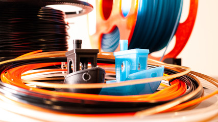 Fototapeta 2 3D printed boats with a variety of 3D printer filament in black, blue and orange. obraz