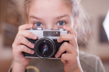 Girl with a retro camera makes a photo.