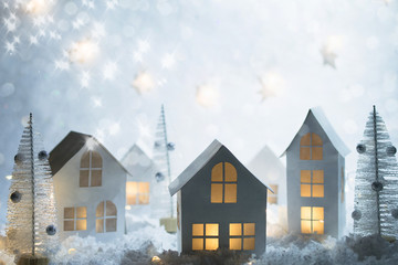 Christmas and New Year miniature magical house in the snow at night and bokeh city lights. Christmas decorations. Holiday concept.