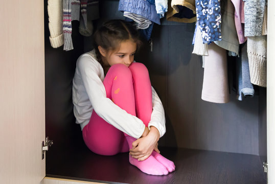 Domestic violence and abused concept. Unhappy and scared little girl hiding in the wardrobe and sitting there down in the mouth