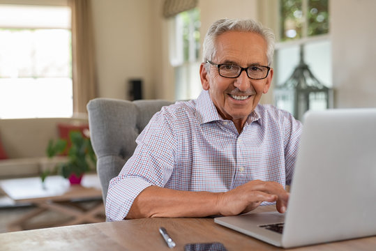 Happy smiling old man with laptop