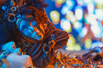 Traditional female carnival venetian mask on blue bokeh background. Masquerade, Venice, Mardi Gras, Brazil festival concept