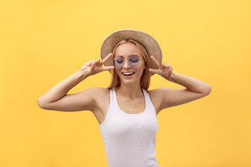 Self portrait of charming cheerful girl shooting selfie on front camera gesturing v-sign peace symbol with fingers isolated on yellow background