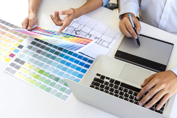 Team of colleague graphic designer drawing and retouching image on graphics tablet and choose color swatch samples for selection on laptop computer
