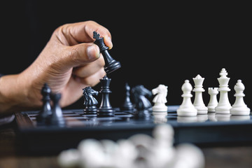 Businessman playing chess and thinking strategy about crash overthrow the opposite team and development analysis for win and successful
