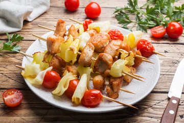 Kebab chicken, zucchini and tomatoes on skewers in a plate. Wooden table.