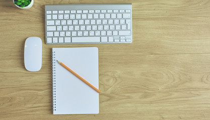 Computer keyboard, mouse and notebook with a pencil on the table
