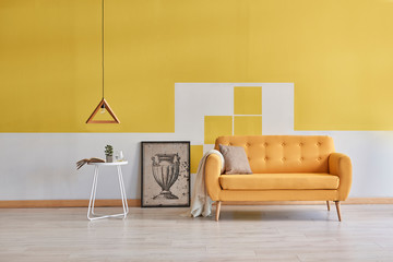 Modern yellow living room, yellow sofa wooden lamp and decorative frame interior.