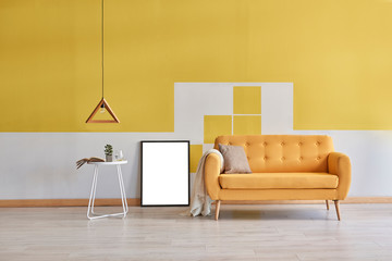 Yellow wall background, yellow sofa and wooden lamp. Empty frame decoration.