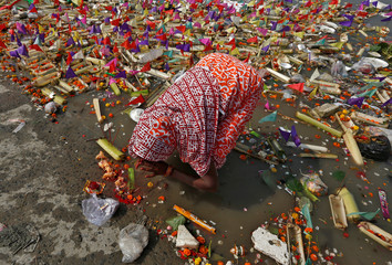 """A woman worships after floating a small decorated boat made with banana stem in the waters of the Ganga river on the occasion of the annual Hindu festival of """"Karthik Purnima"""" in Kolkata"""