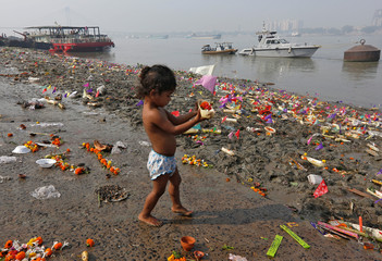 """A child holds a small decorated boat made with banana stem to float it in the waters of the Ganga river on the occasion of the annual Hindu festival of """"Karthik Purnima"""" in Kolkata"""
