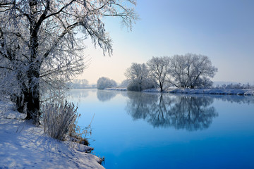 Winter Landscape Reflecting in River, Trees covered by hoarfrost and snow