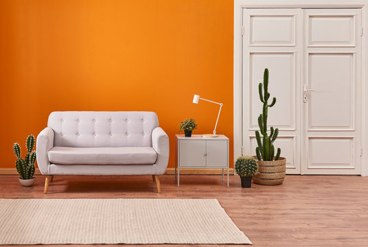 Living room sofa with orange background and white classic door.