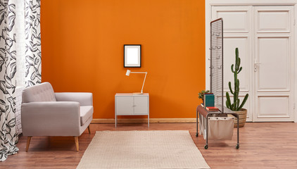 Living room orange wall grey cabinet white lamp frame and grey sofa. Metal unites with curtain.