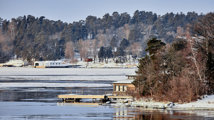 Sweden house in the wintertime. Nature on the shore of the fjord