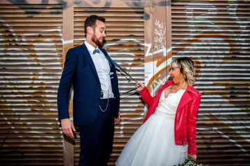 Couple of newlyweds play with suspenders in front of a graffiti metal fence.