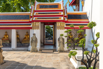Chinese guardian figures beside a gate at the cloister of the Wat Pho temple in Bangkok