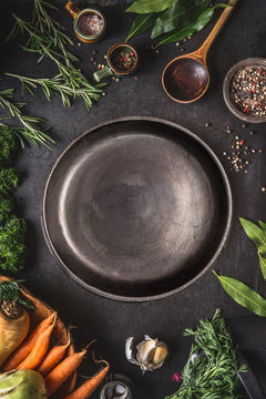 Food cooking and healthy eating background with empty dark rustic plate and fresh seasoning, spoon and vegetables ingredients, top view. Copy space for your text and design