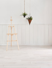 Wooden picture leg, white classic wall and vase of plant interior.