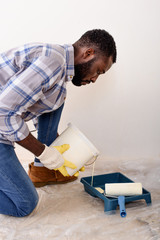 focused african american man in protective gloves pouring paint into roller tray during renovation of home