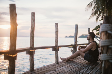A young guy is sitting on a wooden bridge at sunset on the ocean. Handsome man watching sunset by the ocean in Southeast Asia
