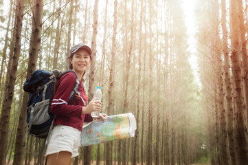Hipster tourist hold and look map on trip, lifestyle concept adventure, traveler with backpack on background forest landscape horizon.