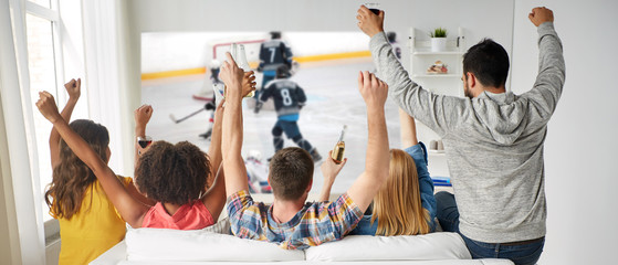 friendship, sport and leisure concept - happy friends drinking beer and watching ice hockey game on projector screen at home