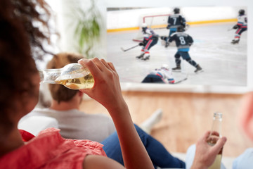 sport, entertainment and people concept - woman with friends drinking beer and watching ice hockey game on projector screen at home