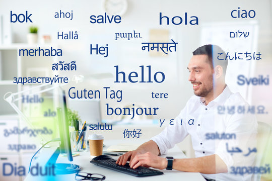 translation, business, and technology concept - smiling male translator or businessman typing on computer keyboard at office over greeting words in different foreign languages
