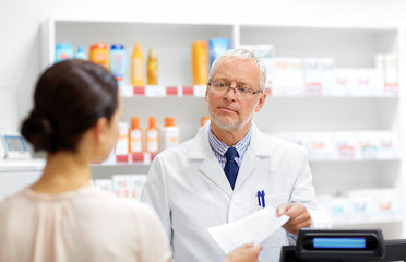 medicine, healthcare and people concept - senior apothecary taking prescription from customer at drugstore