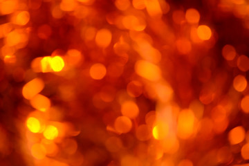 Bokeh. Holiday background. Christmas lights. Glitter. Defocused sparkles. New Year backdrop. Festive wallpaper. Blinks. Carnival. Bokeh retro style photo. Orange.