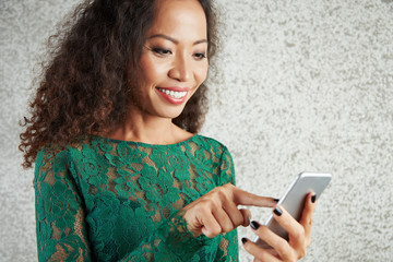Smiling Asian woman with curly hair typing a message on her mobile phone