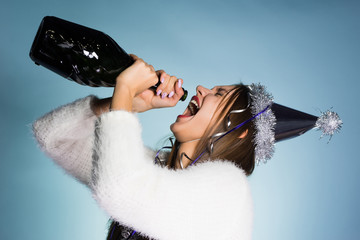 funny drunk young girl celebrating the new year, drinking champagne from the bottle
