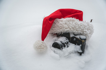 vintage camera in the snow dressed in a New Year's hat, the concept of Christmas holidays and gifts, winter holidays and vacation