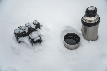 vintage camera in the snow and a thermos with coffee, tea, minimalism, winter photography. top view, the concept of Christmas holidays and gifts for Christmas, winter holidays and vacation