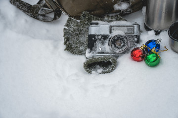 vintage camera in snow, the concept of Christmas holidays and gifts and sale, winter holidays and vacation, backpack, a thermos with coffee and a warm blanket, Christmas decorations