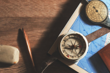 Compass on rustic wood table with vintage tone, top view